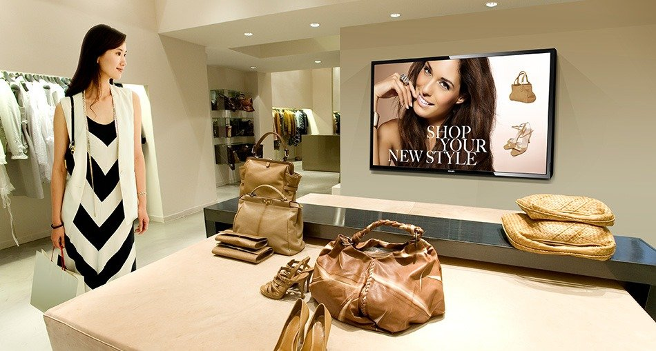 Lady shopping with digital signage nearby